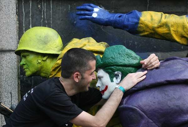 Юни 2011 г. Младеж се снима за майтап с тайно изрисуваните барелефи на паметника на Съветската армия в София, преди те да бъдат почистени от общината. Снимка: Impact Press Group - Sofia Photo Agency