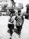 Партизански патрул по улиците на Пловдив, на заден план тържествена арка, издигната за посрещането на РККА (Рабоче-крестьянская красная армия), известна като Червената армия в града, около 9 септември 1944 г. Снимка: Изгубената България - lostbulgaria.com