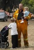 Пожарникар си почива с децата, след като се е борил с огъня в Кинглейк, на 46 км. северно от Мелбърн. Снимка: Ройтерс