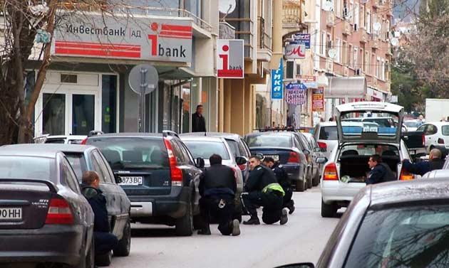 Ченгетата приклякат около банков клон в центъра на Сливен, където маскирани държат заложници. Снимка: Булфото