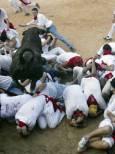 Бик тъпче през купчина налягали участници в надбягванията с бикове в последния ден на фестивала в Памплона. Снимка: Ройтерс