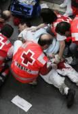 Участник в надбягванията получава медицинска помощ, след като е бил наръган от бик. Снимка: Ройтерс