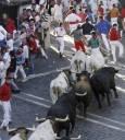 Група бикове гонят по улиците на Памплона участници в надбягванията в последната седма гонка на фестивала в чест на Св. Фермин.