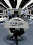 Посетител седи във високотехнологичен стол и гледа видео за екологични коли на щанда на