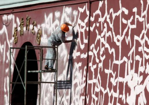 Работник изглажда боядисаните участъци от стена на Забранения град в Пекин. Реставрацията на стената е част от подготовката за предстоящата 60-годишнина от създаването на комунистическата Китайска народна република на 1 октомври 1949 година. Очаква се да има огромен парад в центъра на Пекин за кръглата годишнина. Снимка: Ройтерс