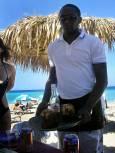 Сервитьор носи пробити кокосови орехи, от които сипва мляко за коктейл с ром