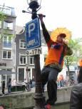 Празнуващ младеж се е качил на стълба на улична лампа и пие оранжева напитка. Снимки: Бистра Величкова