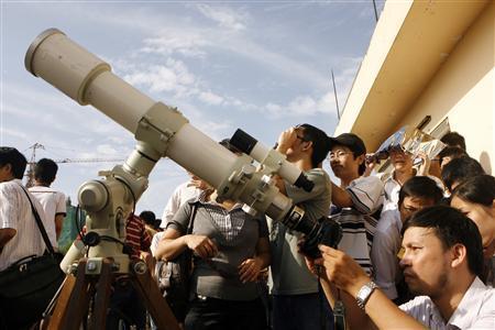 Изследовател снима частичното затъмнение над Виетнам в Ханойския педагогически университет. Снимка: Ройтерс