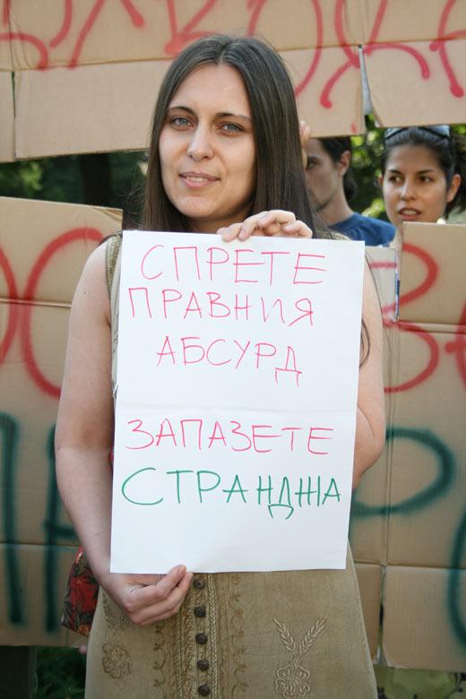 Момиче държи плакат по време на протест в градинката между Парламента и Ректората на Софийския университет.