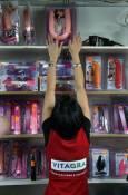 Момиче от щанд на секс шоп сваля от рафта атрактивен артикул, който напомня популярния напоследък виц - Бате Бойко имал два к.ра, всеки един - по-голям от другия. Снимка: Иван Бакалов