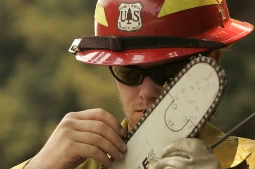 Пожарникар почиства моторната си резачка след борбата за овладяване на големите пожари край Биг Сур, Калифорния.Снимка: Ройтерс