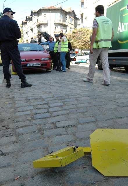 """Веднага след като шофьорът разрязва скобата, закачена на гумата, довтасват служители на """"Паркинги и гаражи"""" и слагат още 4 скоби на колата му - по една на всяка гума. Снимка: Булфото"""