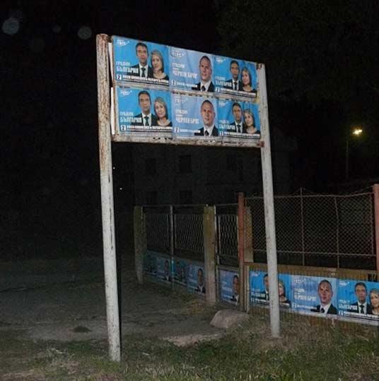 Табела за населено място, облепена с плакати на Плевнелиев. Снимка: fairelections.eu