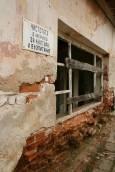 Табела с популярен соцлозунг върху разрушаваща се сграда в Мандрица. Снимки: Нели Томова