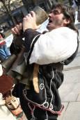 Мъж отпива вино от един от звънците, които са част от кукерския му костюм. Снимка: Нели Томова