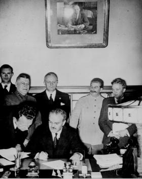 Външният министър на СССР Вячеслав Молотов подписва Пакта за ненападение с Германия на 23 август 1939 г. в Москва. Зад него са Сталин и Рибентроп. Снимка: Национален архив на САЩ