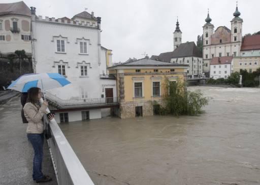 Случайна минувачка набюдава наводнението в Щайр, Горна Австрия. След силните дъждове през последните няколко дни, реките преляха от коритата си и причиниха наводнения в селища в Горна и Долна Австрия. Снимка: Ройтерс