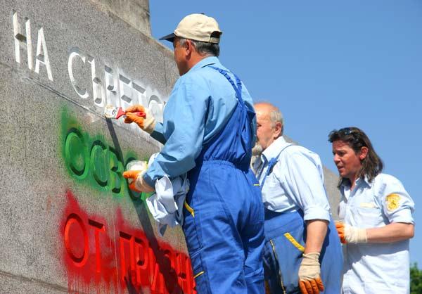 """Работници почистват изрисуваното българско знаме върху надписа """"На Съветската армия освободителка от признателния български народ"""". Чистачите бяха докарани с кола на фирма """"Егида"""" в 9,30 сутринта, след като паметникът за поредна година осъмна изрисуван. Снимки: e-vestnik"""
