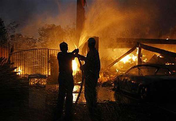 Местни жители опитват да помогнат с градинските си маркучи в гасенето на пожара в Йорба Линда, Калифорния. Огънят, който  се разпространи бързо поради силните ветрове, унищожи около 70 имота в града на знаменитостите Монтесито, в южната част на Калифорния, където миналата година отново имаше големи пожари. Снимка: Ройтерс
