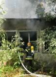 Пожарникар гаси пламъците във вътрешността на запалената къща. Снимки авторката