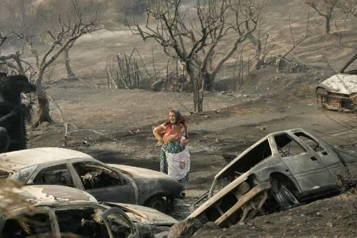 Възрастна жена гледа изгорелите коли в градчето Артемида на полуостров Пелопонес, югозападно от Атина. Снимка: Ройтерс