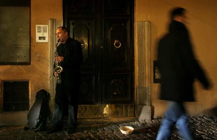 Уличен музикант свири край ресторантче на малка улица. Снимка: Иван Бакалов