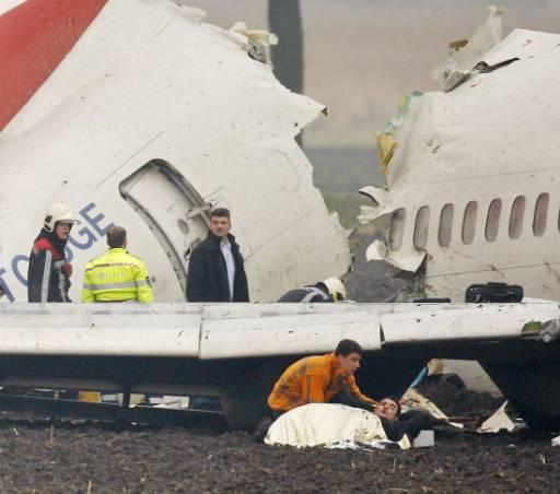 """Пострадал пасажер получава първа помощ до самолета Боинг 737-800 на турските авиолинии, който днес се разби на летище """"Скипхол"""" в Амстердам със 135 души на борда. Авиокатастрофата е станала при опит за приземяване на машината, която излязла от пистата и се е разцепила на три. По последни данни на холандските летищни власти, загиналите са девет. Още над петдесет са ранени, двадесет и пет от тях са с по-сериозни травми. Снимка: Ройтерс"""