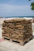 Палет с плочи, оставен край плажа. Из целия град могат да се видят строителни материали, очакващи да влязат в употреба.