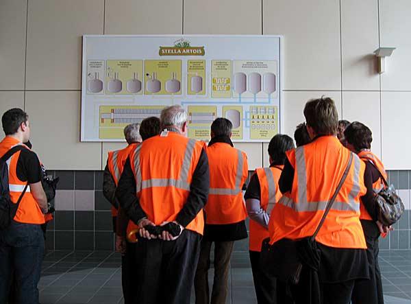 Посетители в пивоварната, облечени в специални предупредителни жилетки, разглеждат схема на производството. Снимки: авторката
