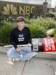 """Стачник е седнал пред централата на компания """"Ен Би Си"""". Снимка: Ройтерс"""