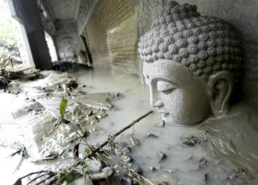 Залята от вода и кал статуя на Буда в провинция Каосюнг, Южен Тайван. Над 700 души от четири села, смятани за пометени от огромни свлачища, се оказаха живи. Те са успели да се изтеглят към по-безопасни терени преди калните маси и скалите да затрупат къщите им. Тайфунът