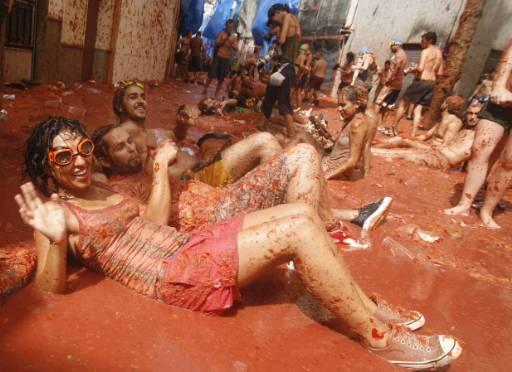 """Участници в """"Томатина"""" махат натъркаляни в доматено пюре след дългия традиционен бой с домати в испанския град Буньол. Снимка: Ройтерс"""