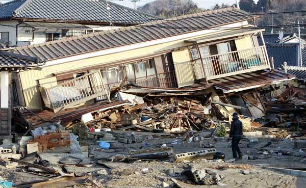 Жители на крайбрежния град Йотсукура край повредени къщи, 4 дни след най-силното земетресение в историята на Япония. Снимки: ЕПА/АП/БТА