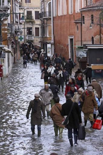 Пешеходци по улиците на наводнения град. Снимка: Ройтерс
